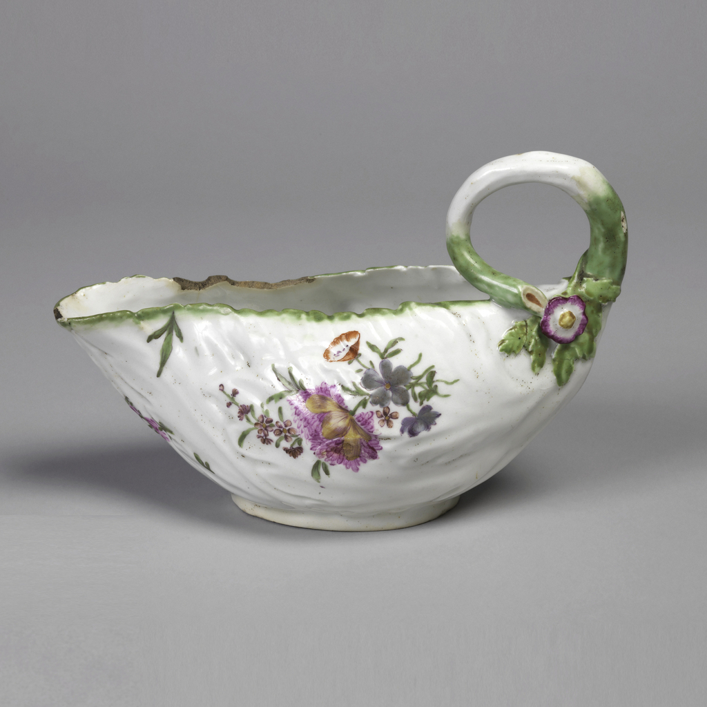 Irregular in shape, with sides modeled in leaf form, and looped handle in shape of a stem, green edge; polychrome sprays of flowers.