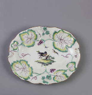 Plate with undulating edges and molded grape vine form. Small molded shells at four sides. Purple enamel at rim. Painted bird on branch at center.