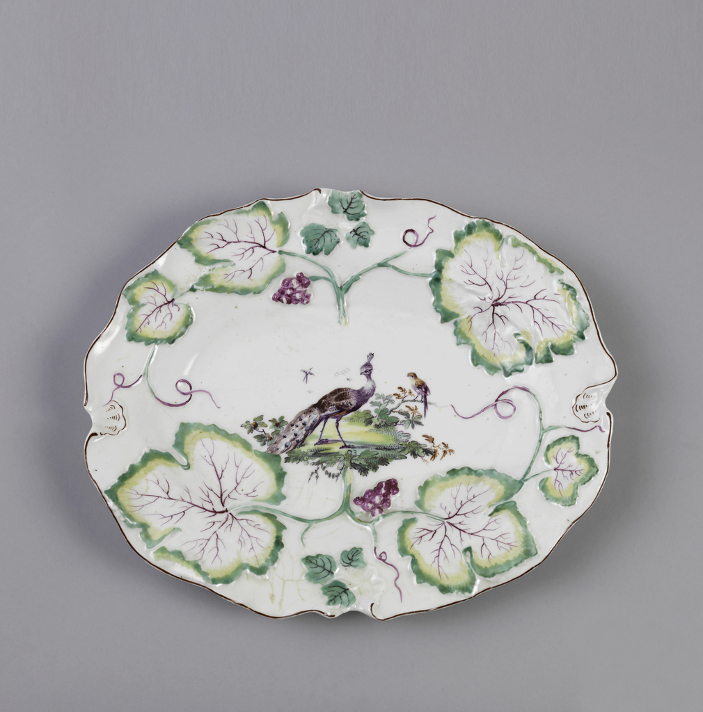 Oval platter with undulating edges and molded grape vine form. Small molded shells at four sides. Purple enamel at rim. Painted peacock at center.