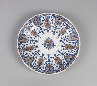 Circular; lambrequin border and central basket of flowers in terracotta color and blue on white ground.