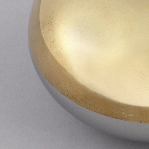Round disc, half brass and half stainless steel; a round impression at top and a circular aperture at bottom (for bottle cap).