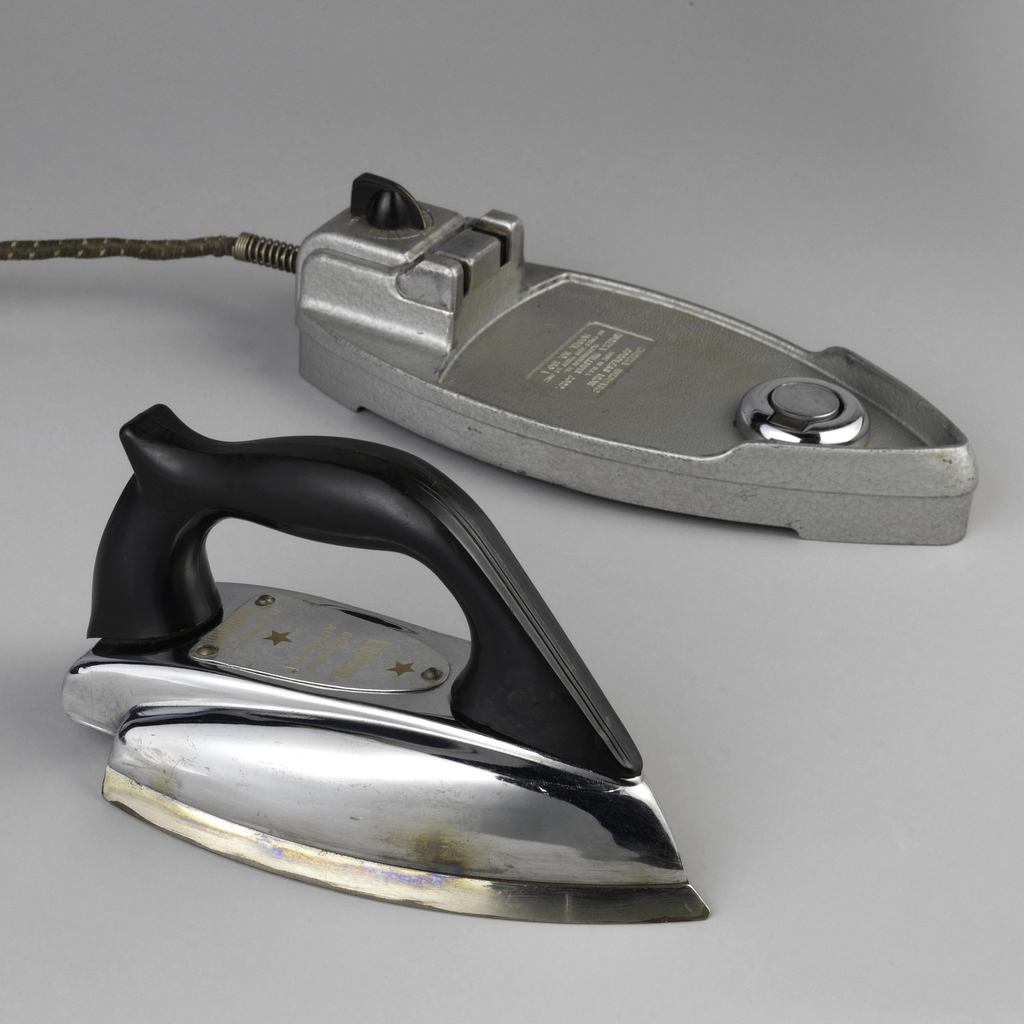 (a) Iron has metal body surmounted by black plastic handle. (b) base is metal and has maker's stamp; with black plastic control dial at the tail.