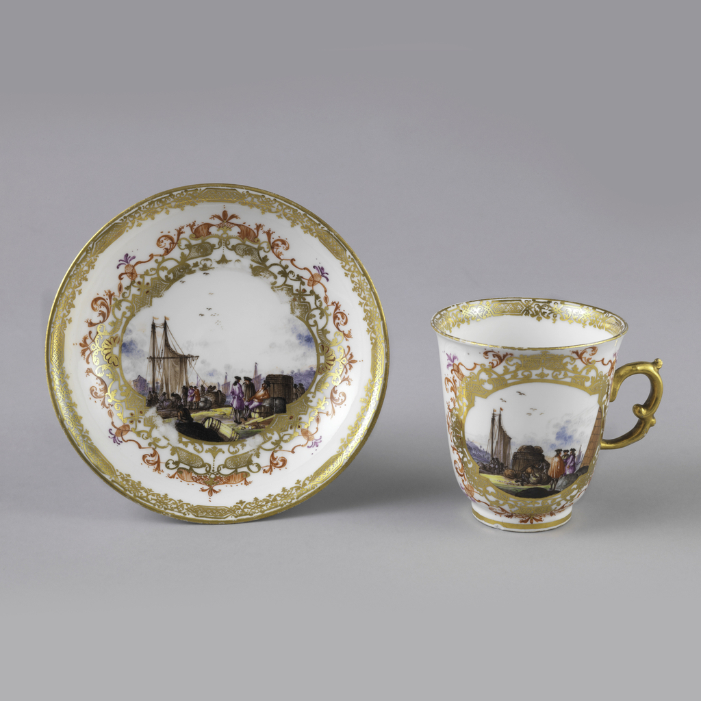 Cup (a) tall, slightly flaring side outcurved at edge; double scrolled handle; cylindrical foot. Saucer (b) shallow, curved side, slightly outcurved at edge. Decoration of seaport scenes - two on cup, one on saucer - enclosed in framework of gilding and orange scrolls