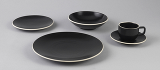Dinner plate (-1), salad plate (-2), bowl (-3), cup and saucer (-4a,b). Plates, bowl, saucer, and cup with loop handle, of circular form in a matte black glaze; rims unglazed, exposing cream-colored stoneware body in contrast to glaze.