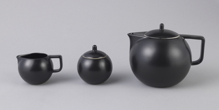 Round, globular form with triangular spout and D-shaped handle that is squared off at the top.  Decorated in a matte black finish.