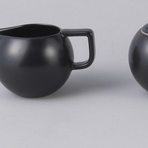 Round, globular form with rounded lid and cylindrical finial that is rounded at the top.  Decorated in a matte black finish.  Creamy stone color peeks out from under area where lid meets bowl.
