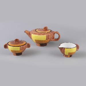 Hemispherical bowl with triangular spout, roughly D-shaped tab handle on side, and low cylindrical foot.  Brushed underglaze decoration of light brown field with geometric panels in yellow, orange and dark brown; dark brown band at mouth, white interior.