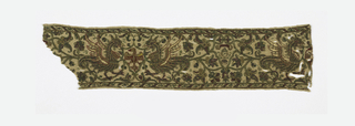 """Border fragment of natural linen embroidered in gold, silver and colored silks, mainly red and green. Design shows a symmetrical arrangement of curving vines and flowers with two wyverns confronted. Between the wyverns is a small eagle with wings spread and head in profile. Within a frame made by the vine tendrils is a ring-like shape with the cypher """"SN"""" or """"CN."""" Much of the gold is laid down over the colored silk producing a luminous quality."""
