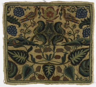 Panel, approximately square, of tan cotton twill, embroidered in several shades of green, blue, brown, ochre and red wool yarns. Symmetrical pattern of leaves, fruit, hillocks with flowering trees, and at the top, a large flower with confronted birds on either side. Narrow border of green and ochre stripes.
