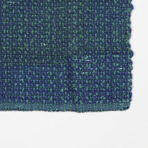 Hand woven sample of predominantly blue-green fabric with texture caused by various yarns.