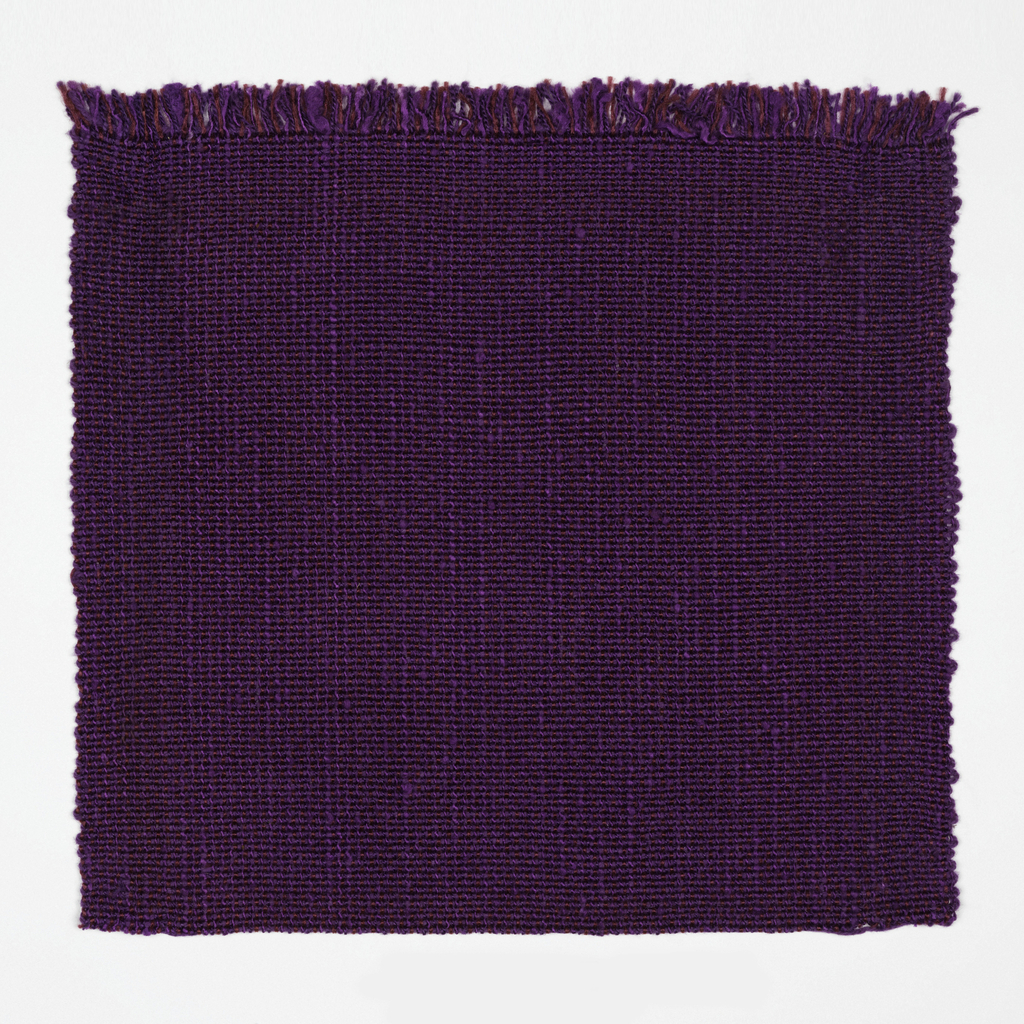 Hand woven purple fabric with a textured surface.