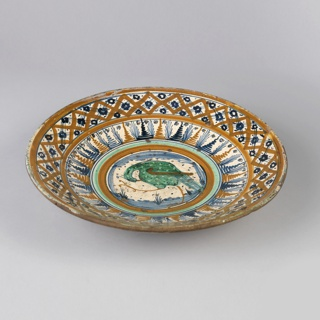 Saucer-shaped, painted in center with green bird within orange and green borders and two outer borders in orange and blue.