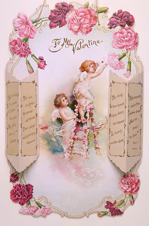 This card depicts two winged cupids at the center with flowers and curved framing surrounding. Above their heads, text in brown: To My / Valentine. One cupid stands on a flower-covered ladder delivering a white envelope with a red heart, as the other cupid looks on, holding the ladder. Flanking them are two die-cut paper vases holding two-dimensional flowers drawn directly onto the card.