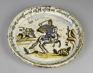 Dish depicting soldier holding a saber on horseback in a landscape with building in left background. Border inscribed in black text.
