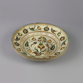 Earthenware dish decorated with floral pattern at center and around rim in yellow, red, and green outlined in black, with inscription in red in center band.