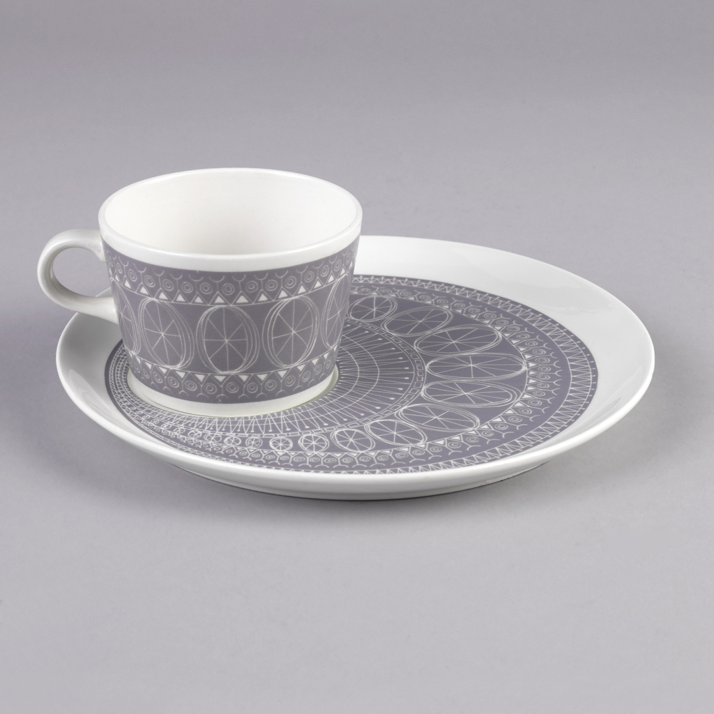 Cup and saucer; cup with loop handle and saucer with area for cup near rim. Both decorated in concentric bands with white line drawings of wheels, zigzags, and circular abstractions on gray ground, with white rim.