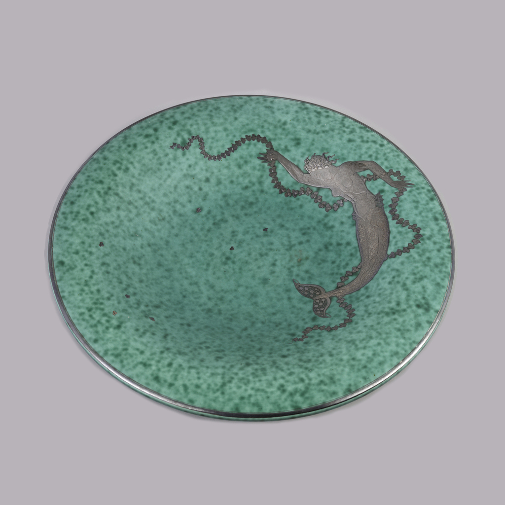 """""""Argenta"""" ware.  Circular plate with molded plain foot ring.  Upper surface concave in center, rising to curved convex plain rim.  Overall mottled blue-green glaze.  Silver inlay on surface of mermaid with one arm raised and one pointed downward grasping leaf garland.  Individual silver inlay leaves scattered across surface.  Mermaid body curved to follow circular edge of plate.  Plain silver band at edge."""