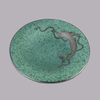"""Argenta"" ware.  Circular plate with molded plain foot ring.  Upper surface concave in center, rising to curved convex plain rim.  Overall mottled blue-green glaze.  Silver inlay on surface of mermaid with one arm raised and one pointed downward grasping leaf garland.  Individual silver inlay leaves scattered across surface.  Mermaid body curved to follow circular edge of plate.  Plain silver band at edge."
