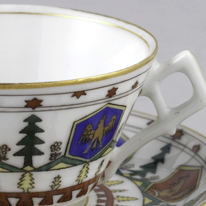 Decorations of red and blue hexagonal cartouches with animals; between the cartouches green trees, above red stars and below, yellow trees and a red line with dents on cup with straight flaring side and curved saucer.  Angular handle on cup.
