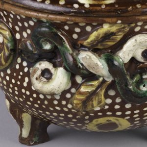 Bowl with feet and lid, dark red-brown with allover white dots; applied twisted leaf and ribbon motifs; lid has yellow circles and finial of large green and white curls topped with green spherical knob.