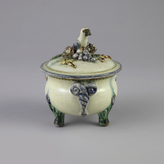 Bowl with green feet; sides have twisted blue plant-like elements. Lid with bird finial on top of grapes, flowers, and leaves.