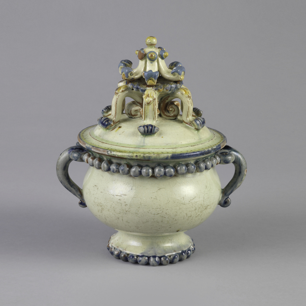 Bulbous two-handled footed bowl. Bowl is white with row of pearls on foot in blue, blue handles, and pearls under rim. Lid's finial is six-footed curled element second element on top in blue, yellow, and red.