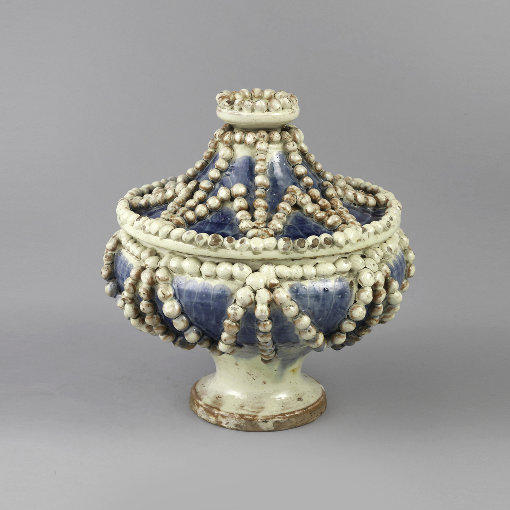 Blue footed bowl with star pattern of white pearls all over. Finial made up of crown of pearls.