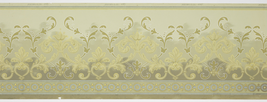 A repeating design of intertwining pale beige and tan acanthus leaves. The lighter ones forming fleur-de-lys, on a steel gray-green into pale green, textured background, below a border of connected circles. Printed in metallic green, gold, pale beige, tan and silver.