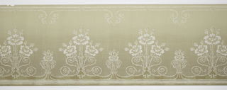 A repeating floral candelabra design connected by swirling stems to a complementary smaller candelabra on a hatched background within a stem bordered design. Printed in white, olive green, taupe and dark brown.