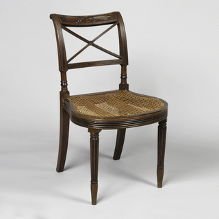 "Both chairs, rounded and reeded seat rail; rounded and reeded tapering legs.  Top rail carved with ""thunderbolt design,"" tied with bow.  Below top rail, two diagonal, crossing bars, reeded."