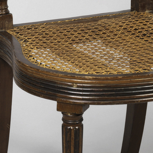 """Both chairs, rounded and reeded seat rail; rounded and reeded tapering legs.  Top rail carved with """"thunderbolt design,"""" tied with bow.  Below top rail, two diagonal, crossing bars, reeded."""