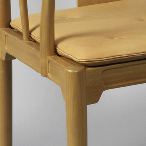 Thick back rail positioned towards center of chair, thin crest rail continuous with thin arms tapering outwards.  One spindle placed diagonally on each side of chair, slanting frontwards from point of position on the seat frame.  Four legs taper from top to bottom.  Seat upholstered in leather.