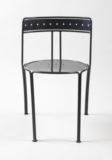 Black chair with circular seat with nine holes framed by tubular border that continue to become two legs in front; the two tubes at back join two other tubes that lead to support of back; back is horizontal band with holds, framed by tubular border; two tubular slats run down the middle of back.
