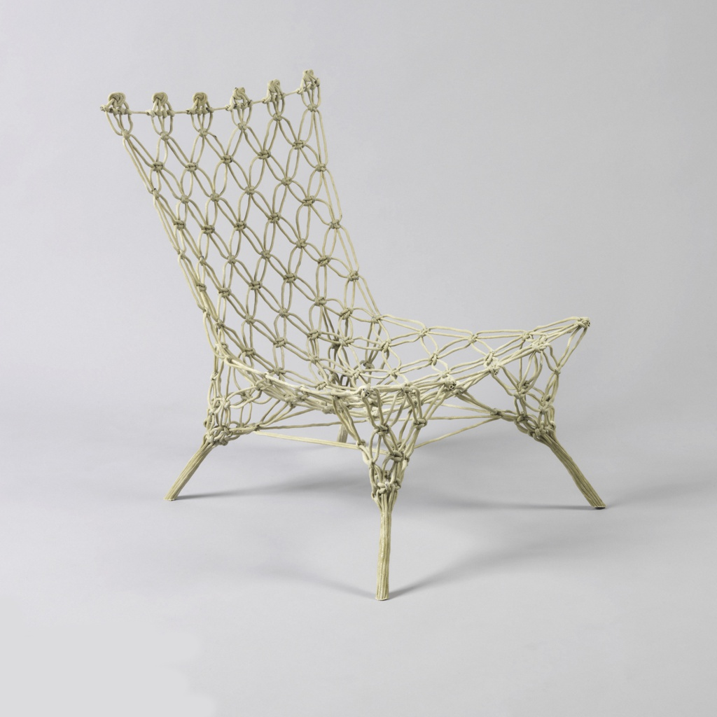 Rigid, epoxy-impregnated, light green one-piece form composed of aramid fiber rope criss-crossed and knotted into the shape of a low four-legged chair.