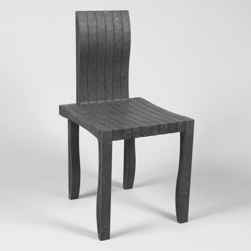 Black rectilinear form with curved edges, composed of 10 consecutive L-shaped modular units forming seat and legs.