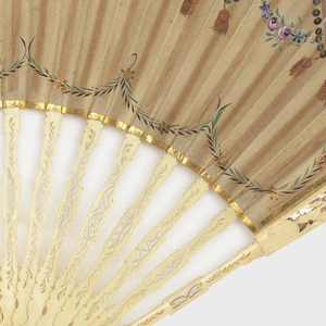 Folding fan with carved and pierced bone sticks. Paper leaf is painted in gouache on the obverse with swags in blue, green and pink with gilt and sequins. The reverse is painted with small sprays of flowers.
