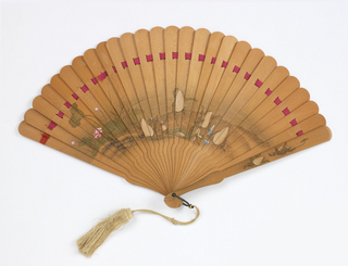 Brisé fan of painted, unvarnished wood. Obverse has a design of dancing frogs with blue and white porcelain. Reverse shows bamboo trees with a bird and dragonfly. Beige tassel.