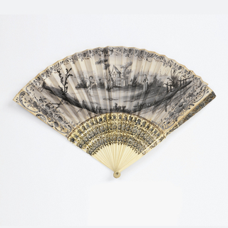 Pleated fan. The paper leaf is painted in black and white gouache. On the obverse, a pastoral scene of two women and a boy in front of a house in a rural landscape, with floral borders. On the reverse, a small sketchy landscape with a house, in black. Ivory sticks carved and painted with flowers in black, gray and white.
