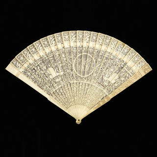 "Brisé fan. Ivory sticks finely carved in designs of landscapes with human figures, birds, and flowers with initials ""A.G."" in medallion; rows of small metal discs."
