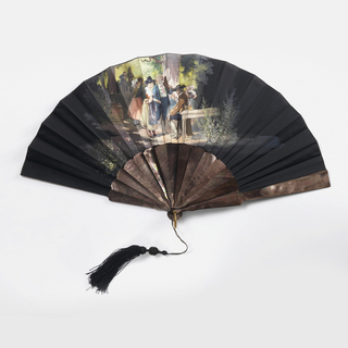 Pleated fan. Leaf and obverse are black taffeta painted with scene of a party under trees with a standing young couple in front of a seated man in the foreground. Reverse is plain. Sticks and guards are plain dark-colored mother-of-pearl with fancy black silk tassel.
