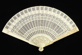 Brisé fan. Ivory sticks pierced and carved with florals, stripes and a shield in center containing monogram RH (?) in Spencerian letters. Landscape carved on guard.