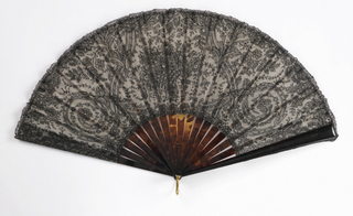Pleated fan. Leaf of black chantilly bobbin lace with design of a flower basket in center and scrolls on each side, backed with white georgette crêpe. Guards and sticks of tortoise shell.