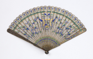 Brisé fan. Metal filigree sticks with polychrome enamel. Guards are solid metal molded with landscape, figures and engraving.Green connecting ribbon.