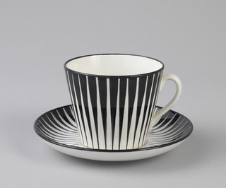Straight-sided, tapering circular cup (a) with glazed decoration consisting of series of narrow black vertical wedges on white ground; black along edge of rim; white loop handle and white interior. Circular saucer (b) with upraised rim and same tapering black decoration on white ground; black at rim; white underside.