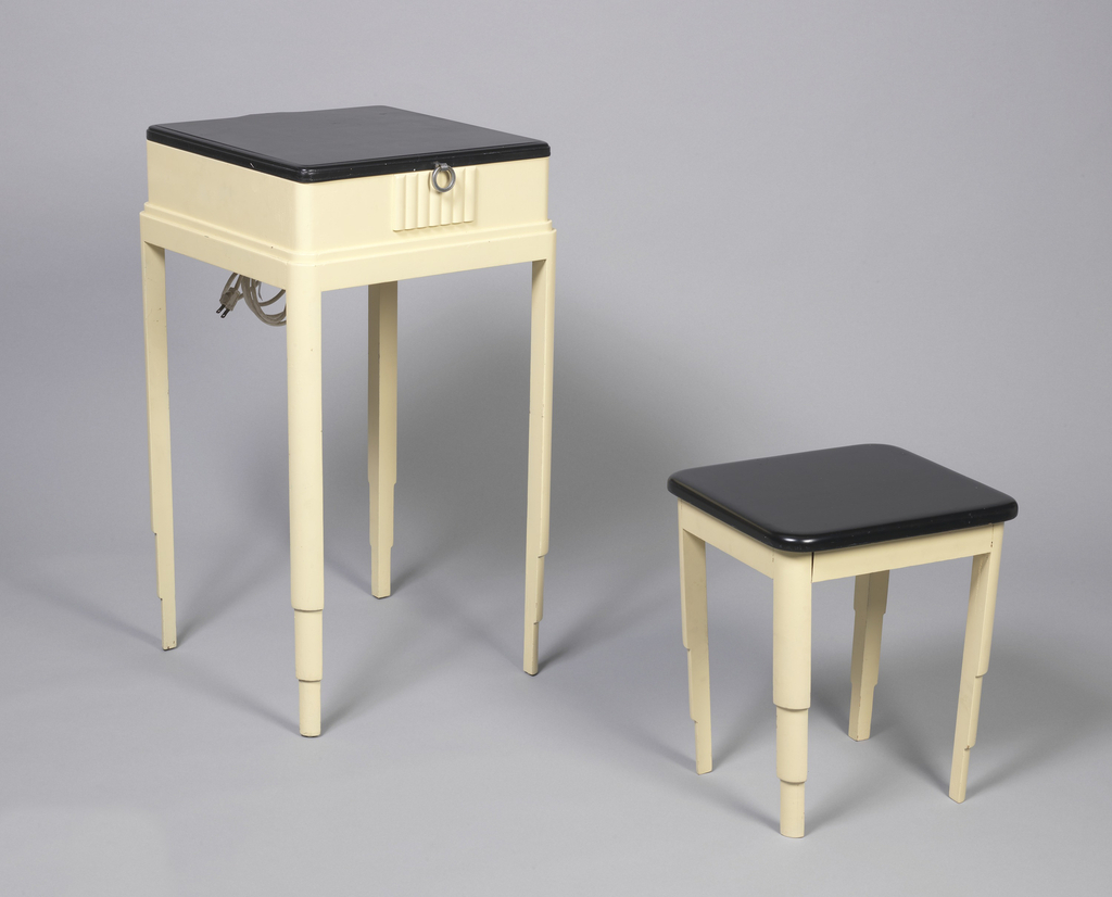 Square-topped vanity table with black-lacquered lid, hinged at back, that opens to reveal mirror and two long lights, with tapered and stepped legs.