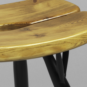 Stool with roughly oval, light colored pine seat of two curved and contoured sections, mounted on four splayed, tapering legs of black-lacquered beech wood.