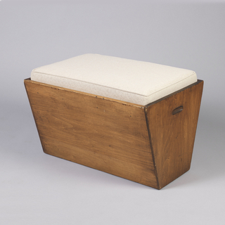 Simple rectangular, tapering box-type base of dark brown wood, two recessed grips on either side; thin, rectangular cushion of woven beige fabric sits in top of base.