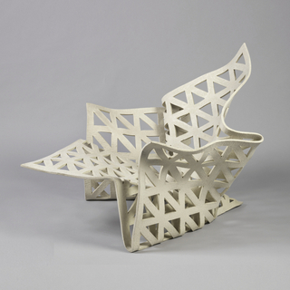 Triangular cut-out shapes in gelatin-infused cream felt chair structure that repeats the triangular form and is based on the shape of a crumpled used handkerchief.