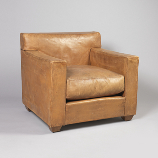 One of set of three of armchairs, characterized by its square shape and matching tan leather.  The armchair's base, very bulky, rests on four wooden feet.  The seat cushion is padded.