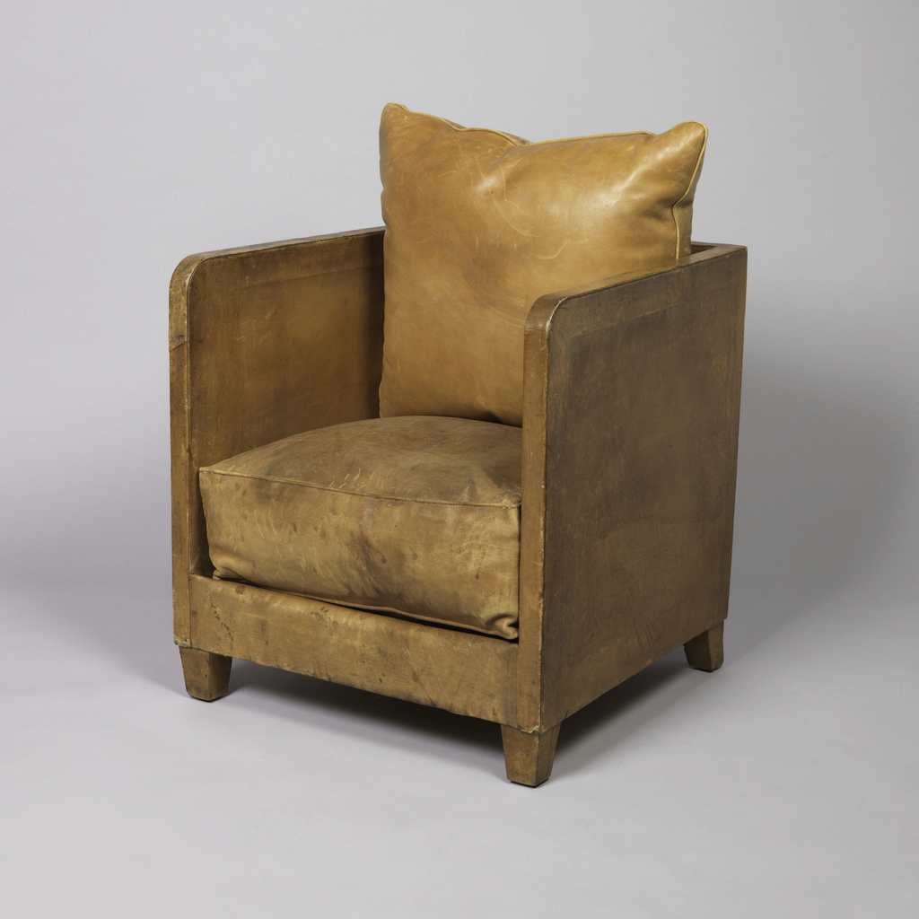 This armchair is covered in tan leather with two cushions.  As part of the chair's rectangular side panel, the armrests are oblong-shaped and thin.  The armchair rests on four wooden feet.